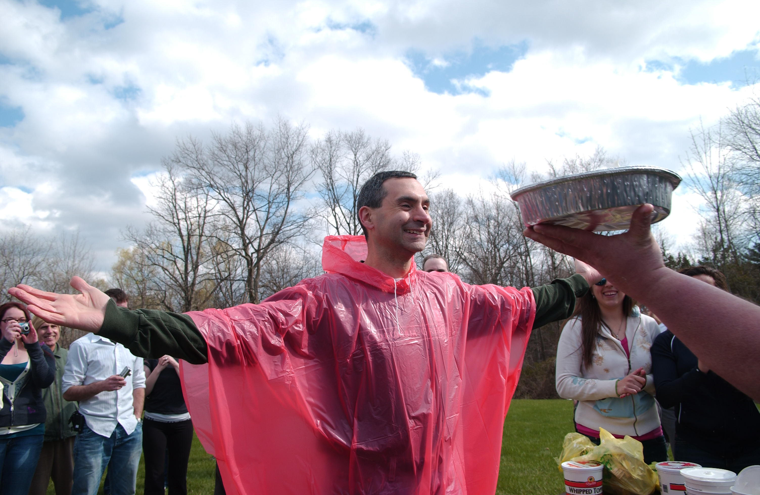 Professor in red poncho readies to take a pie to the face
