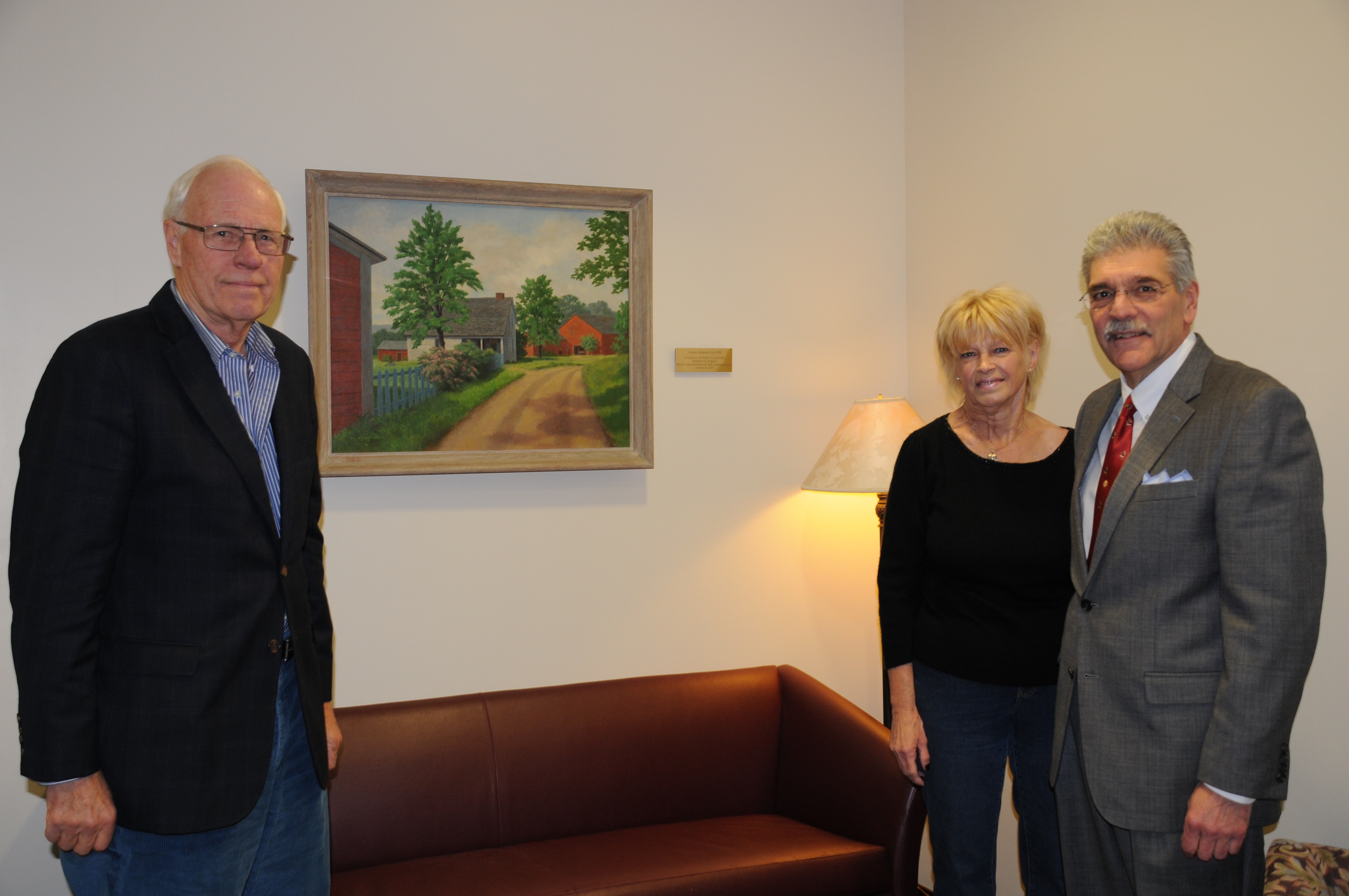 Three people stand with oil painting