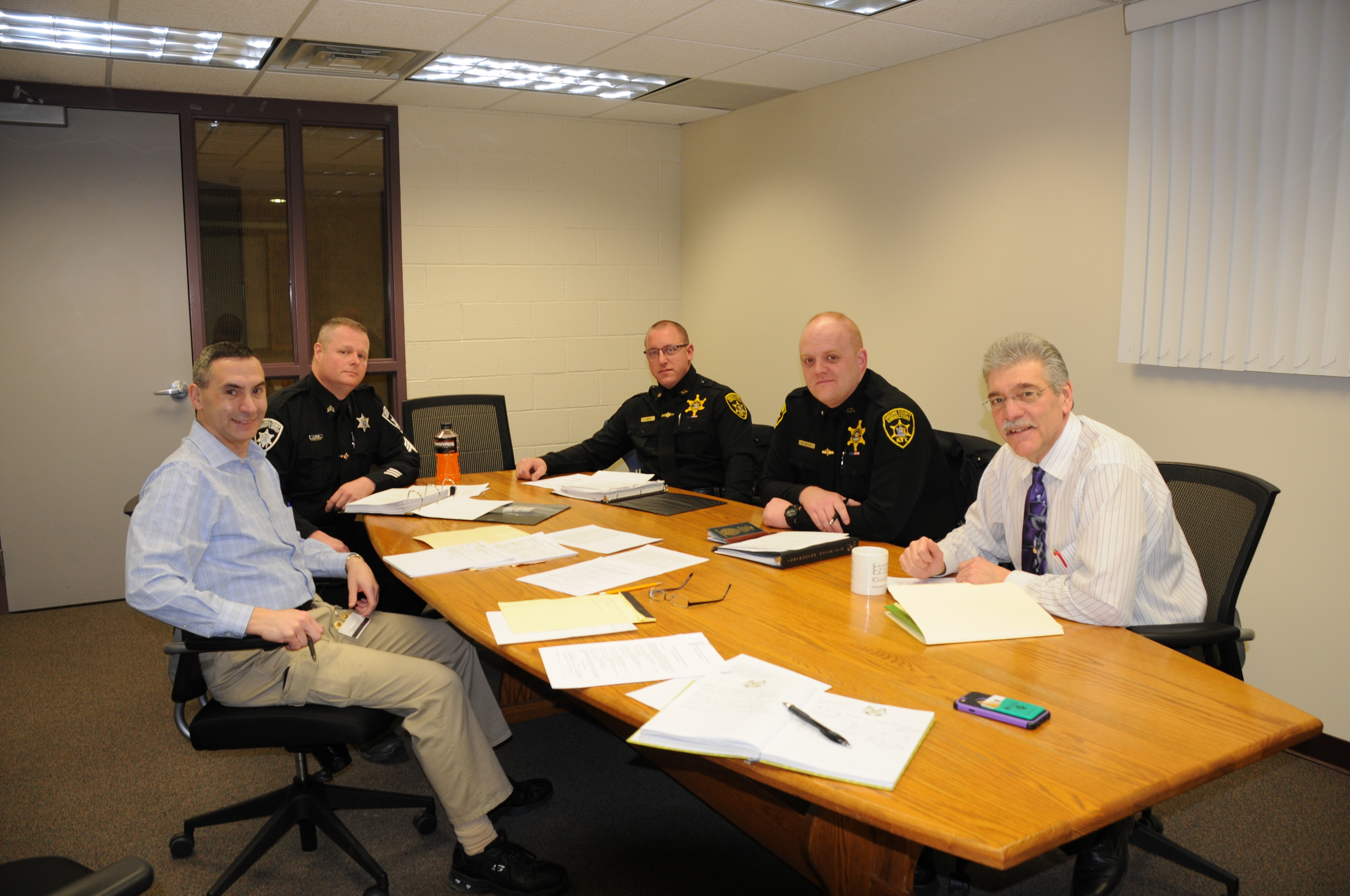 Three corrections officers and two professors at a table