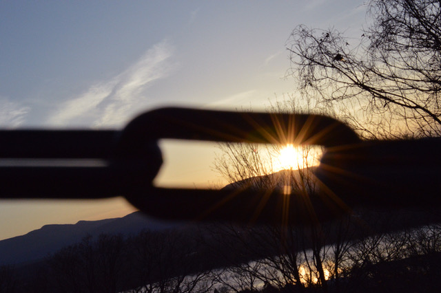 Chain Link with sun behind it