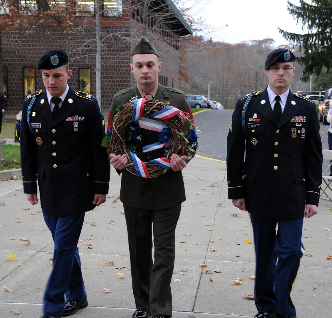 three military personnel with wreath