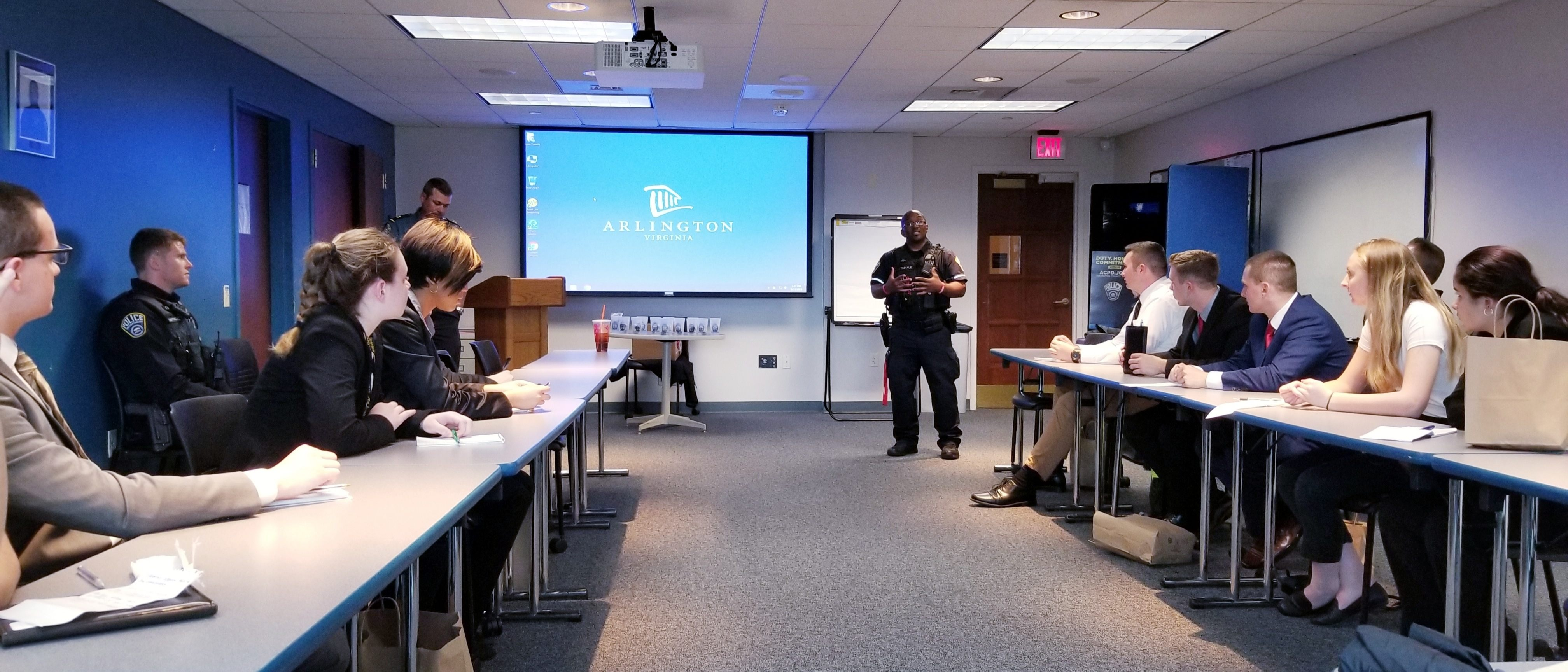 Police officer speaking to college students in a boardroom