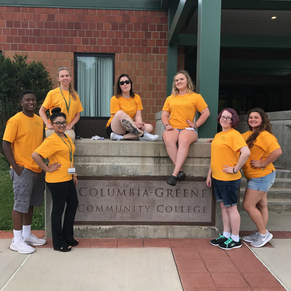 seven students in yellow shirts posed around a stone columbia-greene community college sign