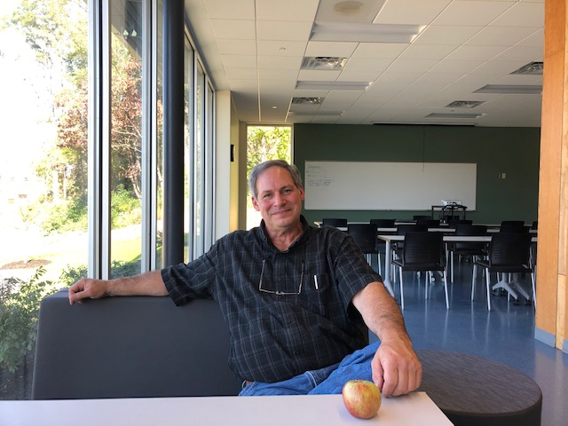 Professor sits at a desk with an apple on it
