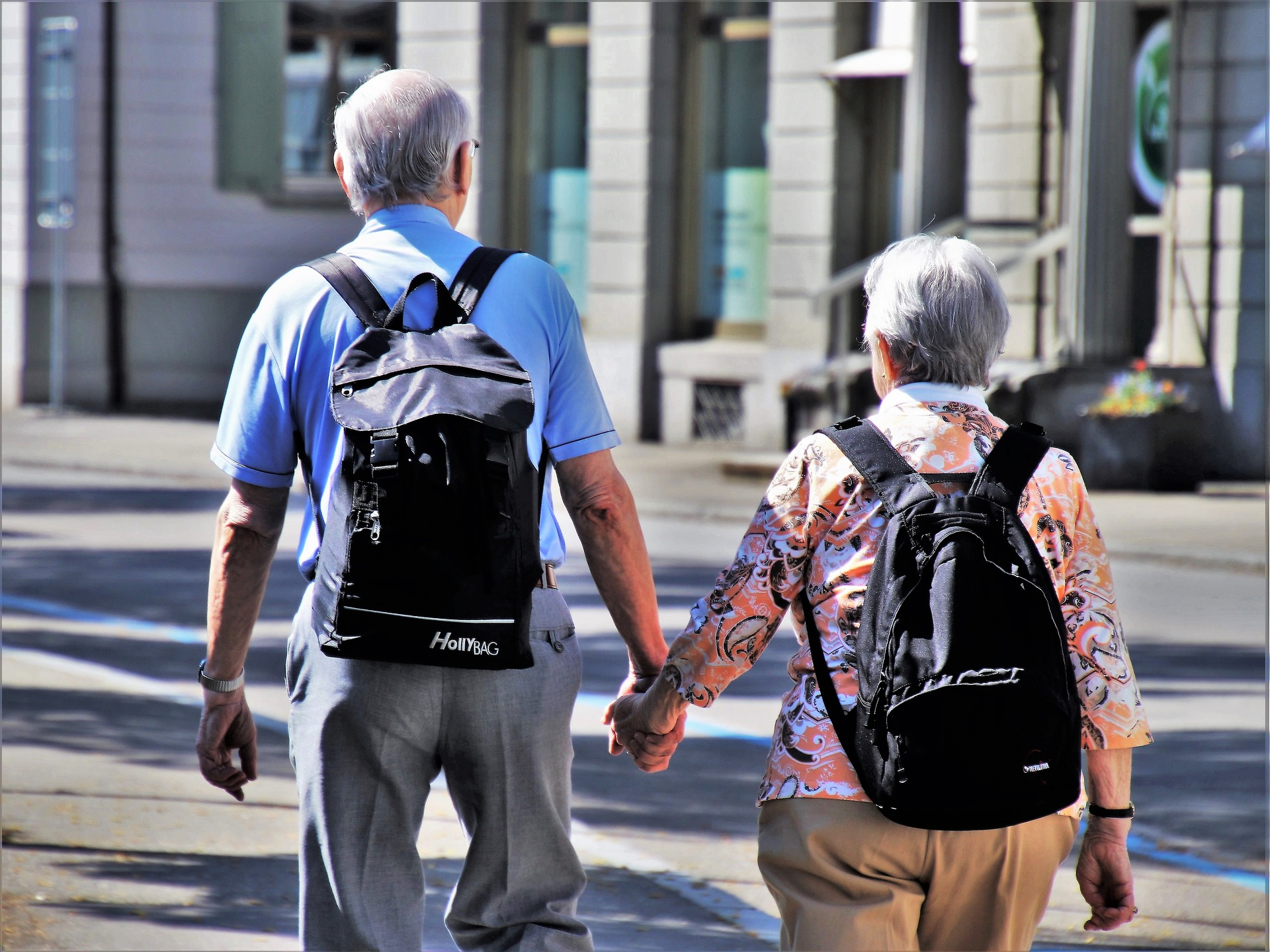 Two senior citizens holding hands with backpacks on