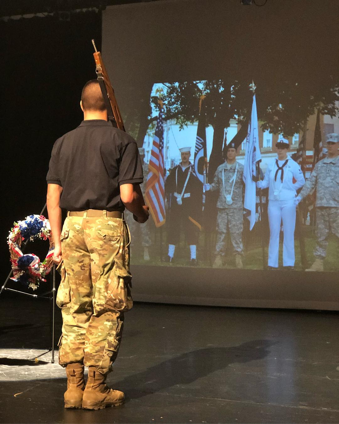 Army color guard soldier looks at photo of other service men and women projected on a large screen