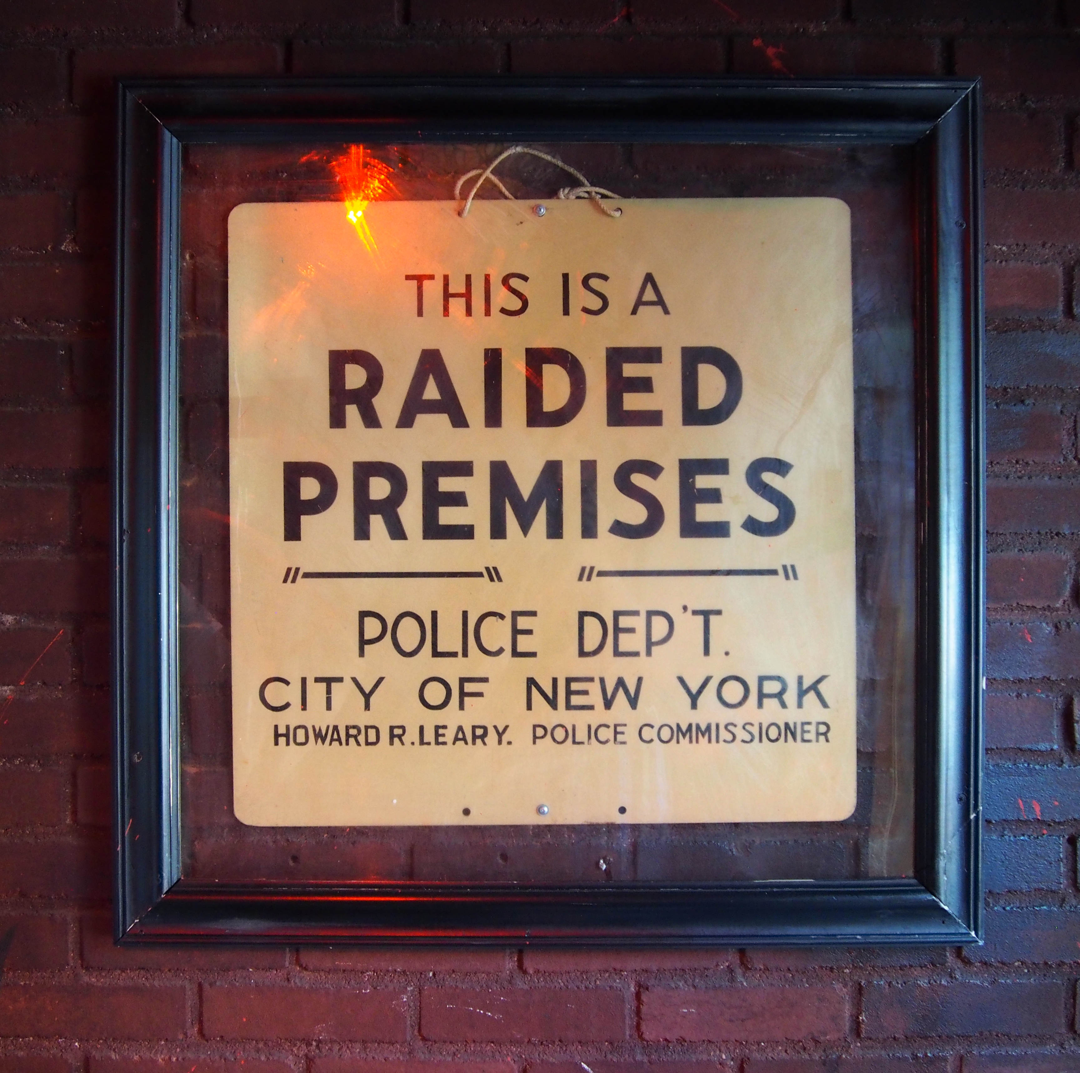 Sign on a brick wall that reads This is a Raided Premises, Police Dept. City of New York