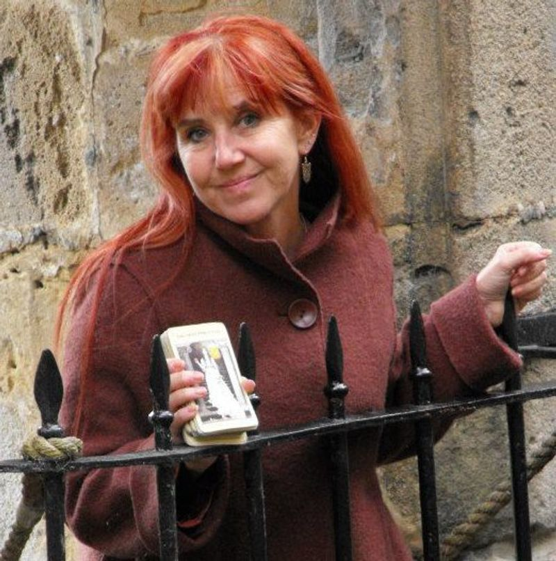 instructor with red hair holds a deck of tarot cards next to an iron fence