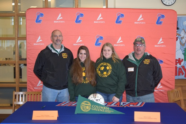 four people at an athletic signing two students female and two coaches male