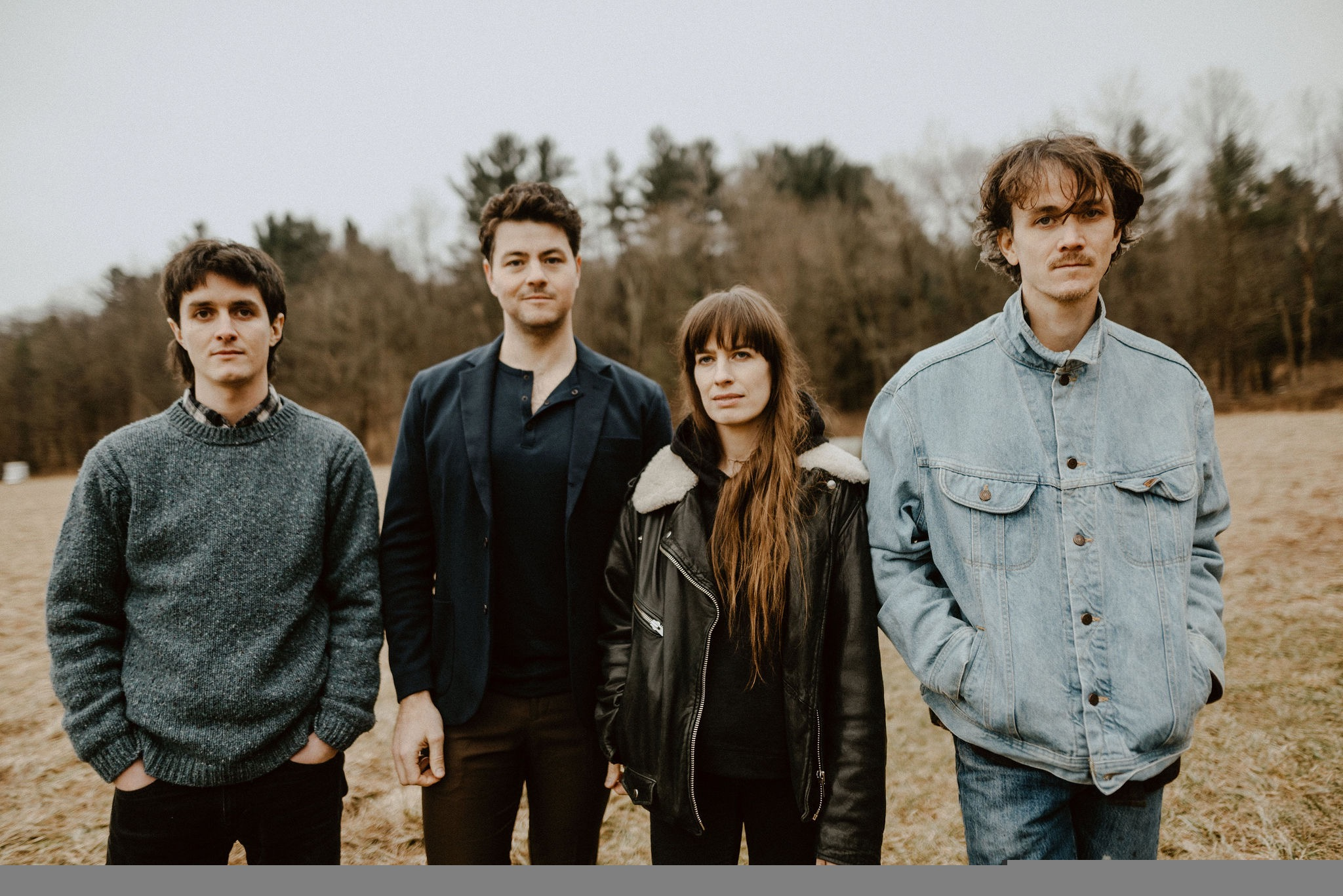 four people, three men and a woman, standing in a field. It's a band photo