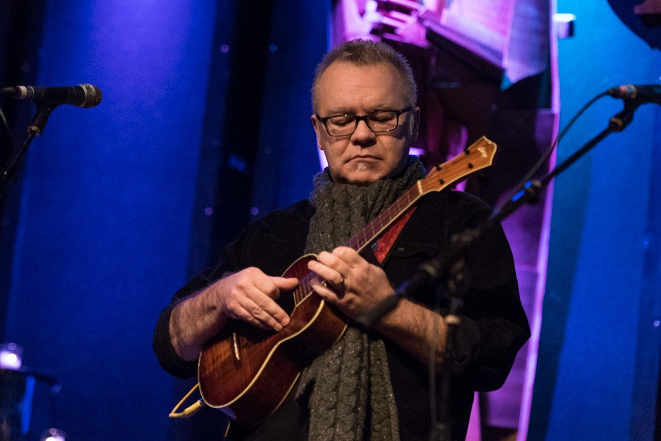 man with glasses playing ukulele on a stage