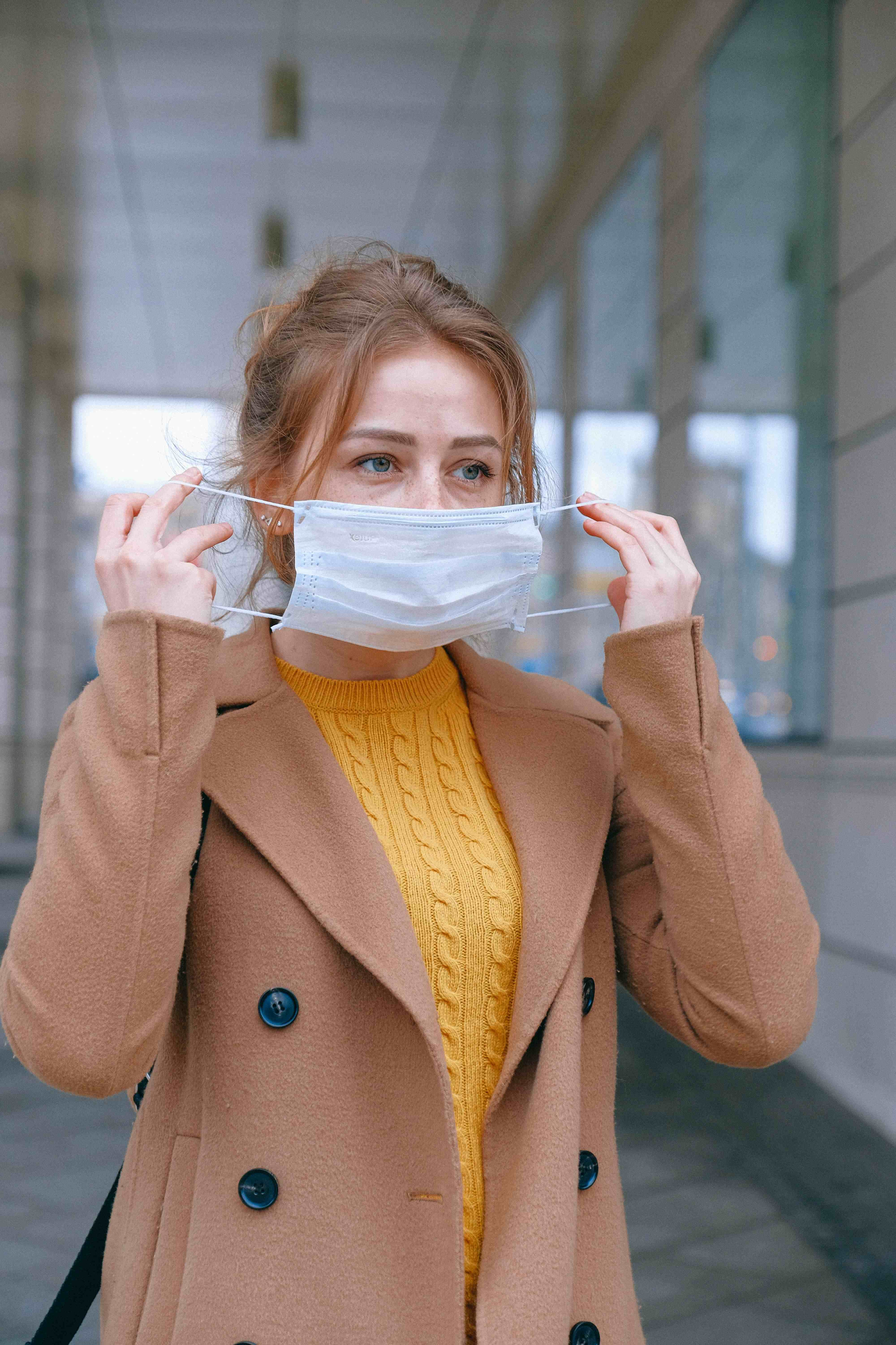 Woman putting surgical mask on outside