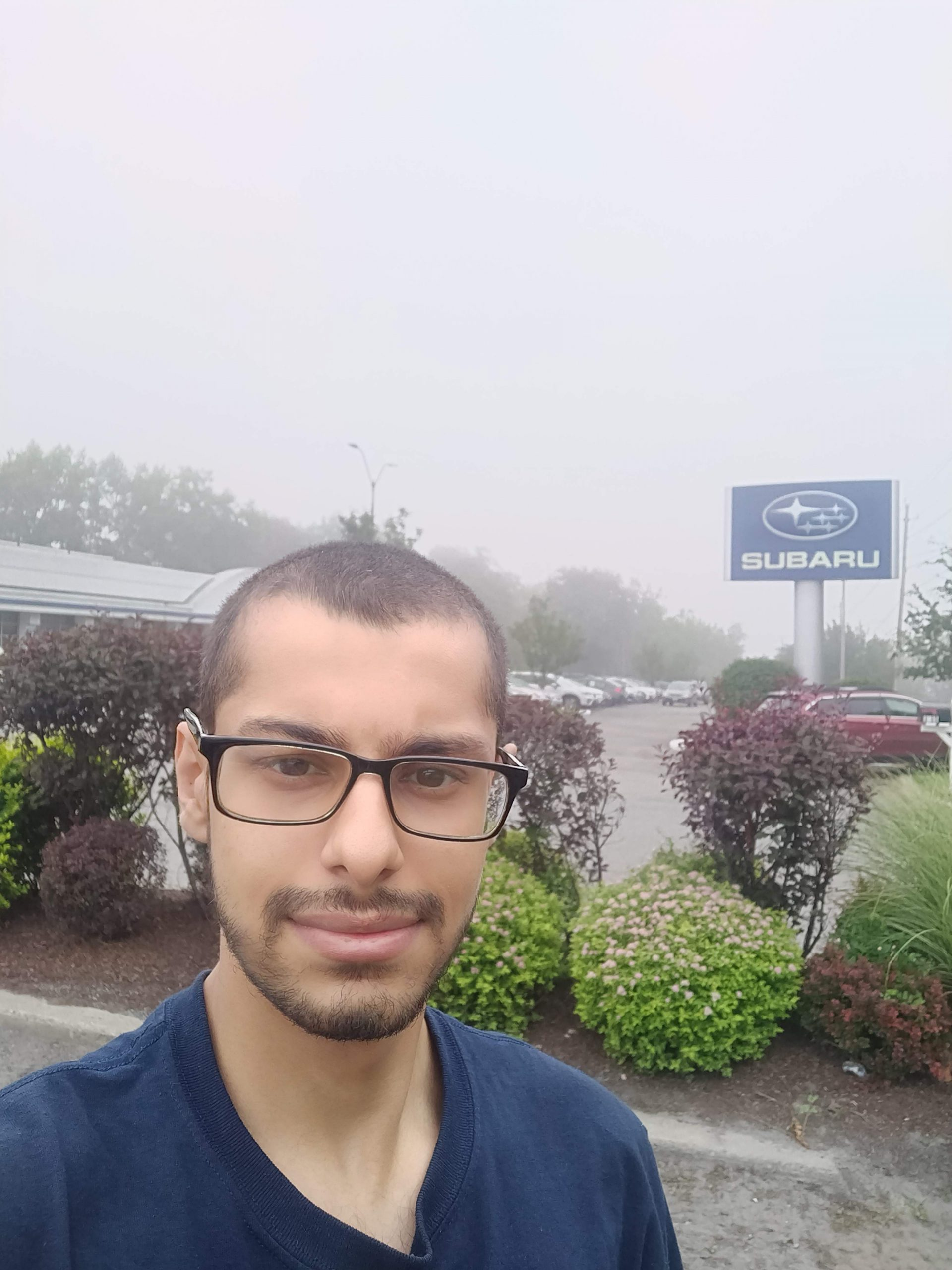 student with black glasses in front of subaru sign