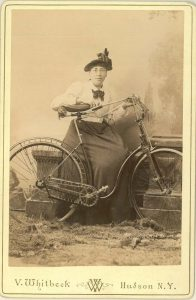 sepia photo of woman from 1800s with her bicycle