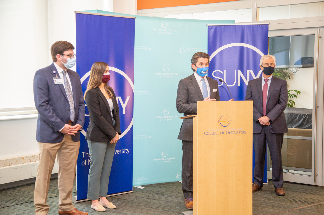 Chancellor Malatras at podium in front of blue SUNY sign with two students standing to his left - one is masculine and one is feminine. all are masked.
