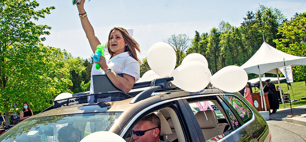 graduate in nursing white uniform waving out of the sunroof of a car in a parade. the car has white balloons on it and the nurse is blowing bubbles.