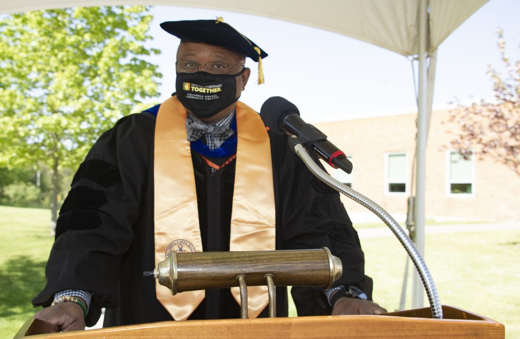 man wearing academic robes and a face mask at a podium