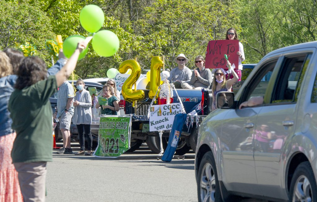 photo of spectators with signs cheering on graduates in cars