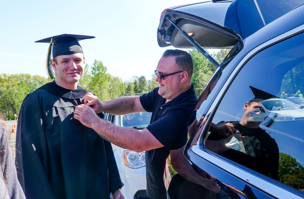 male student in cap and gown being pinned with a bouttonierre by another man