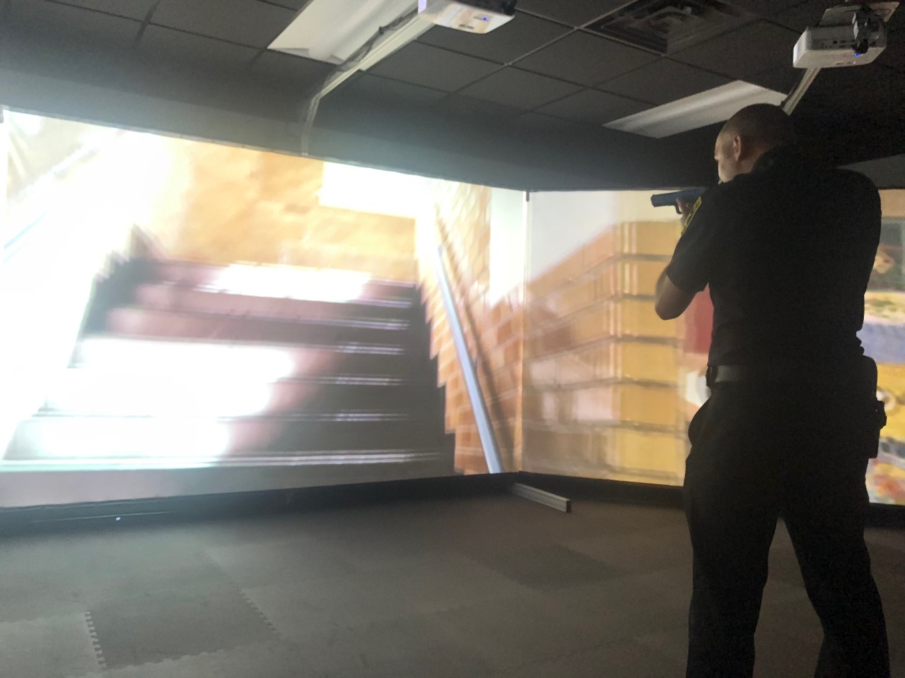 police officer holding faux weapon in front of a three-screen array showing a video. Officer is engaged in a school-shooter simulation in a Use-of-Force Simulator Room