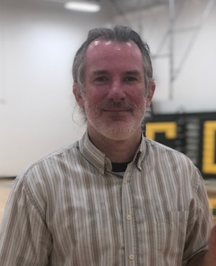 headshot of man with grey ponytail standing in a gymnasium