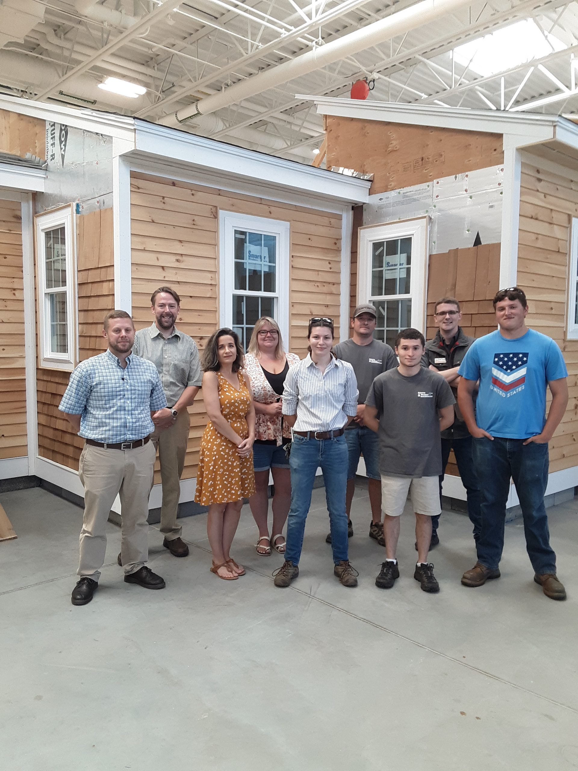 A group of nine people standing in front of a wood structure under construction
